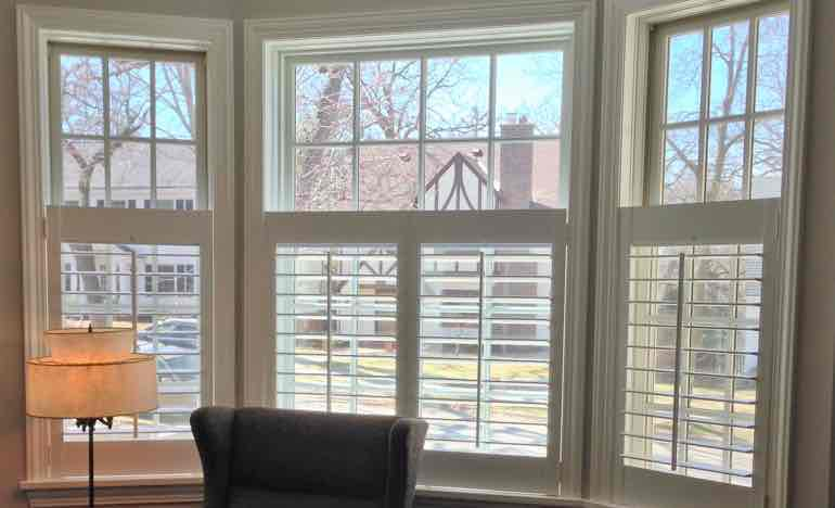 Half-length insulating shutters in family room bay window.