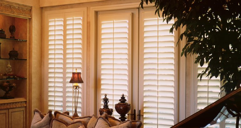 Plantation shutters on windows and door in San Antonio parlor