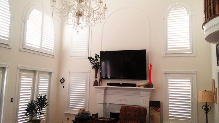 San Antonio great room with mounted television and arched windows.