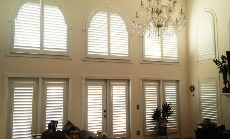 Great room in two-story San Antonio home with plantation shutters on high windows.