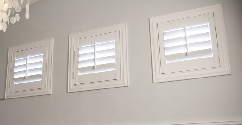 White shutters on small windows in laundry room