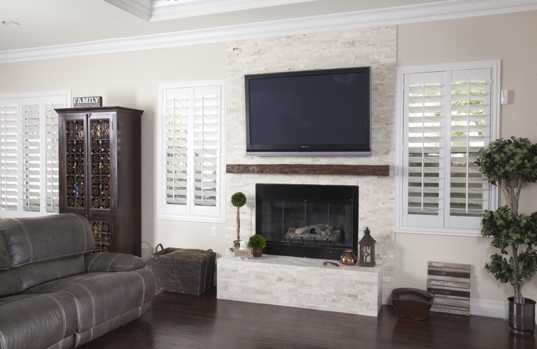 White plantation shutters in a San Antonio living room with solid hardwood floors.