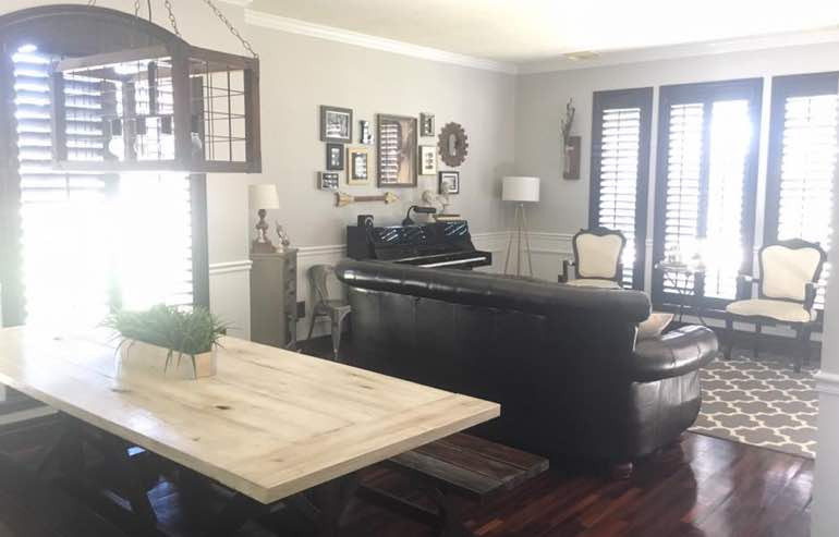 Wood shutters in family room windows by Sunburst Shutters San Antonio.