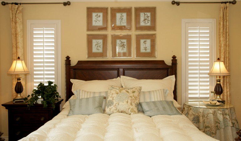 Tall plantation shutters framing bed in a bedroom in San Antonio