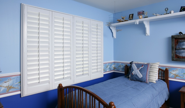 Blue kids bedroom with white plantation shutters in San Antonio